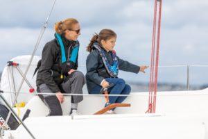 Mutter und Tochter auf Segelschiff tragen Rettungswesten