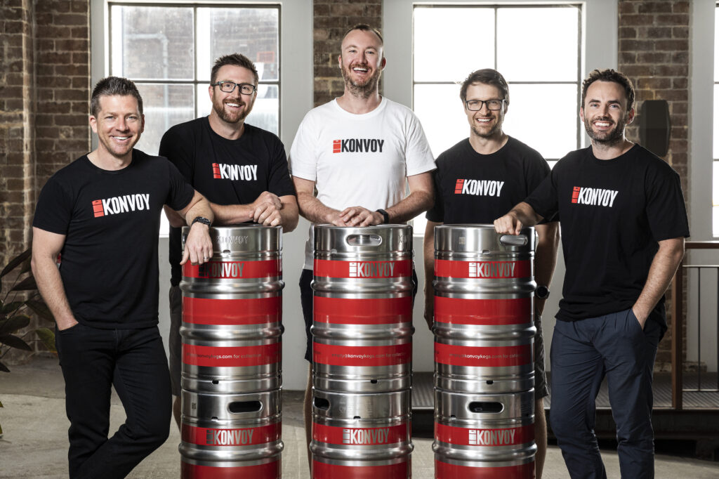 Team der Konvoy Group vor Getränkefässern